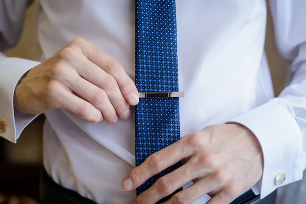 The man straightens his tie closeup