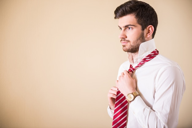 A man straightens a tie on his neck.