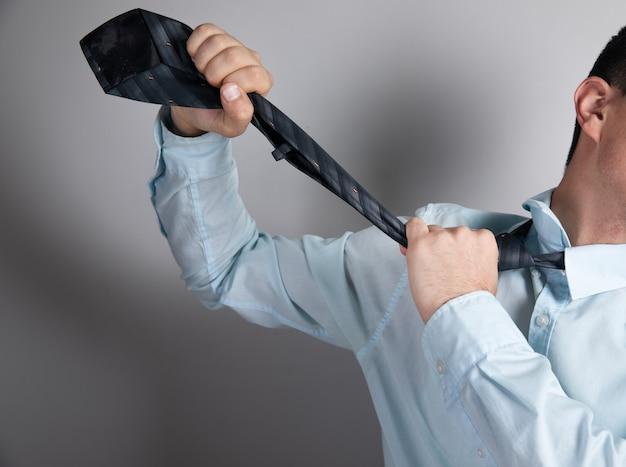 남자는 회색 표면에 넥타이로 목을 졸라 죽인다.