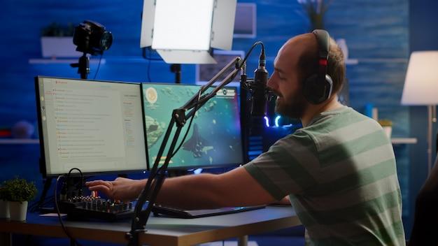 ゲームの競争でストリームチャットとマイクでプレーヤーと話しているrgb強力なコンピューターでスペースシュータービデオゲームを実行するミキサーでサウンドをチェックするマンストリーマー。プレイヤーマンストリーミング