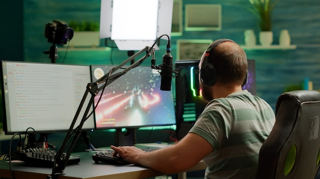 남자 스트리머는 헤드셋을 사용하여 공간 사수 비디오 게임을 하고 스트림 채팅과 마이크에 대해 이야기합니다. 게임 토너먼트 중 rgb 강력한 전문 컴퓨터에서 온라인 스트리밍 사이버 수행