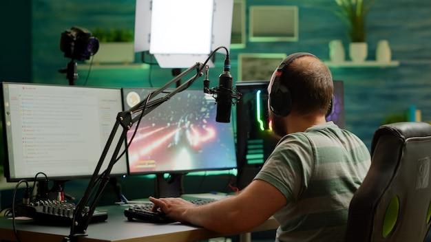 Streamer uomo che gioca al videogioco sparatutto spaziale utilizzando l'auricolare, parlando in chat in streaming e microfono. cyber streaming online che si esibisce su un potente computer professionale rgb durante il torneo di gioco