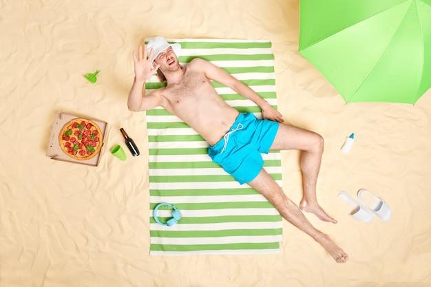 男は太陽の光から腕を隠します笑い顔はビーチアクセサリーに囲まれた海辺で日光浴をする緑の縞模様のタオルの上に日よけ帽の青いショートパンツを着ています。緩和時間の概念