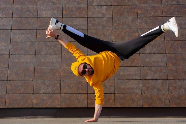 マンストリートブレイクダンサーが通りで踊っています。 bboyはアクロバティックな要素をフレアにします。