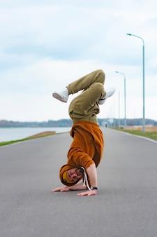 マンストリートブレイクダンサーが通りで踊っています。 bboyはアクロバティックな要素をフリーズさせます。