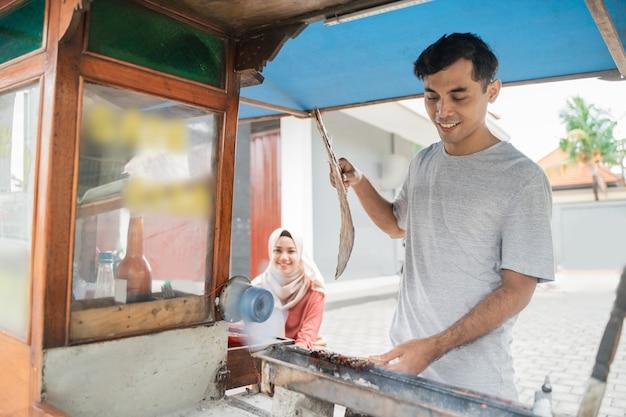 Sate ayam를 판매하는 음식 카트와 치킨 satay의 남자 길거리 음식 판매자
