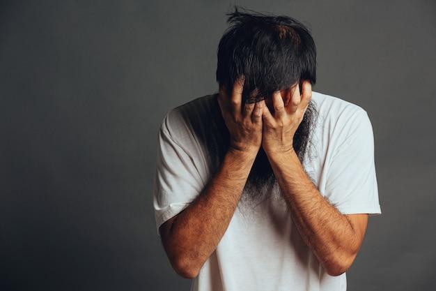 남자는 스트레스를 받고 손으로 얼굴을 가린다.