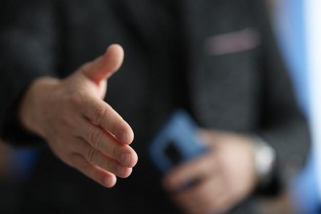 Мужчина протягивает руку для рукопожатия крупным планом