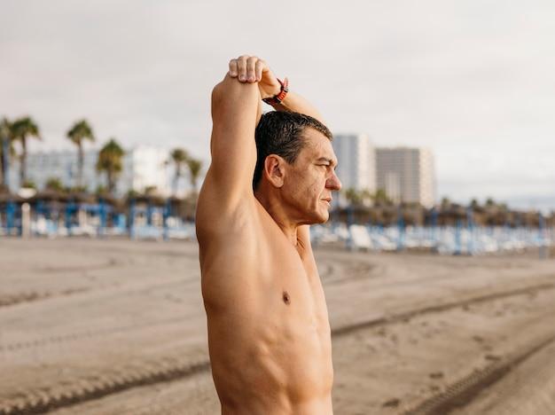 Человек, растягивающийся на пляже, вид сбоку