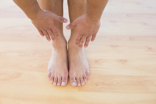 Man stretching hands towards his feet on parquet floor