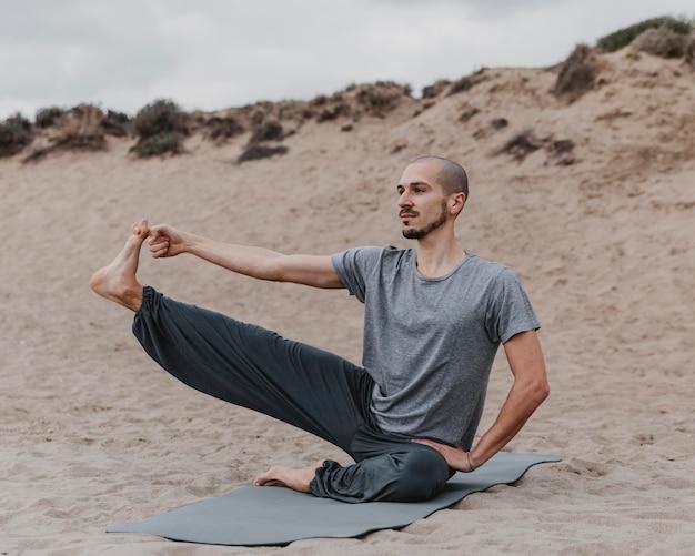 Мужчина растягивает ногу во время занятий йогой на открытом воздухе