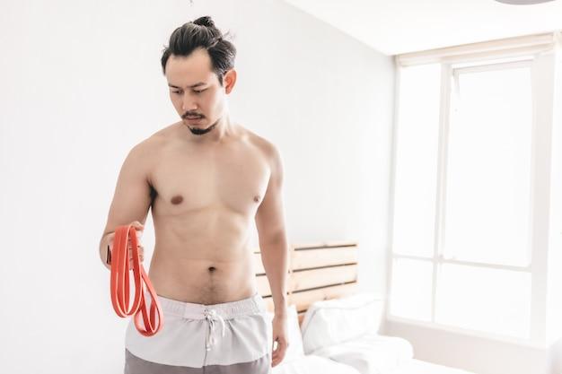 Укомплектуйте личным составом протягивать его мышцу в концепции разминки дома с диапазоном сопротивления.