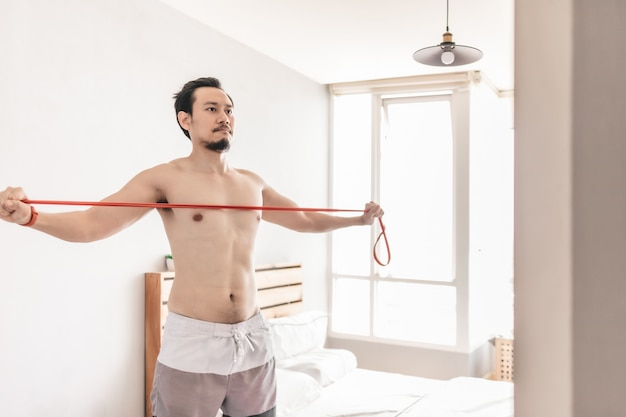 Man stretching his muscle with resistance band.