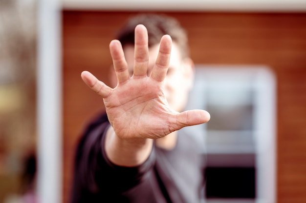 Man stretching out hand over blurred house