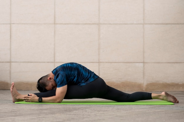Man stretching outdoors while doing yoga