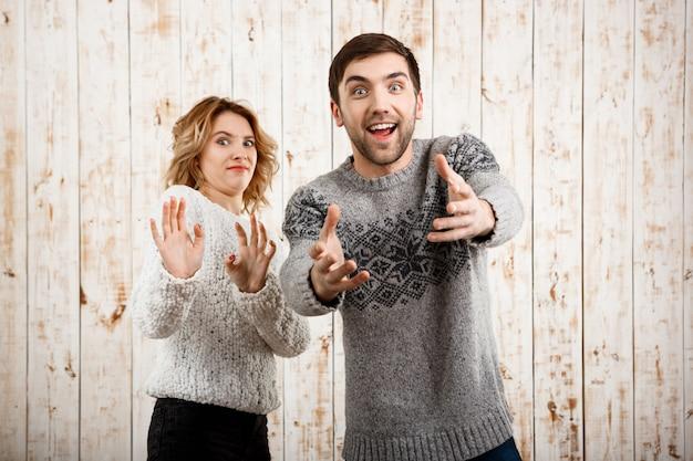 Мужчина растягивает улыбающуюся девушку на деревянной стене