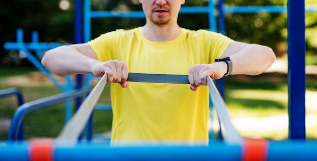 Мужчина растягивается с эластичной резиной во время уличной тренировки