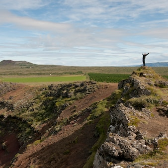 Man stretching with open arms on rocky hill outcrop above agricultural lands
