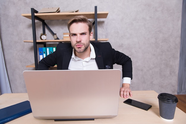 男はオフィスで厳格なひげを生やした上司のトップマネージャー。 ceoのコンセプト。今すぐオフィスを出てください。就職の面接に失敗しました。従業員の解雇。カメラを見て気難しい上司。機嫌が悪いラップトップを持つ上司。