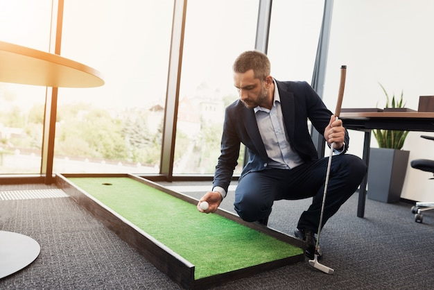 Man in strict business suit plays in an office in mini-golf.