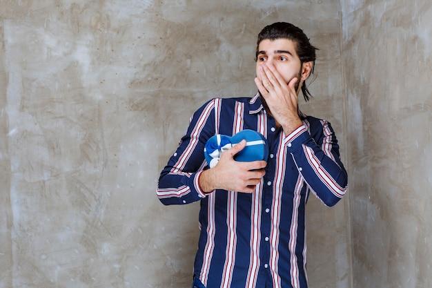 Uomo in camicia a righe con in mano una scatola regalo blu a forma di cuore e sembra elettrizzato e spaventato