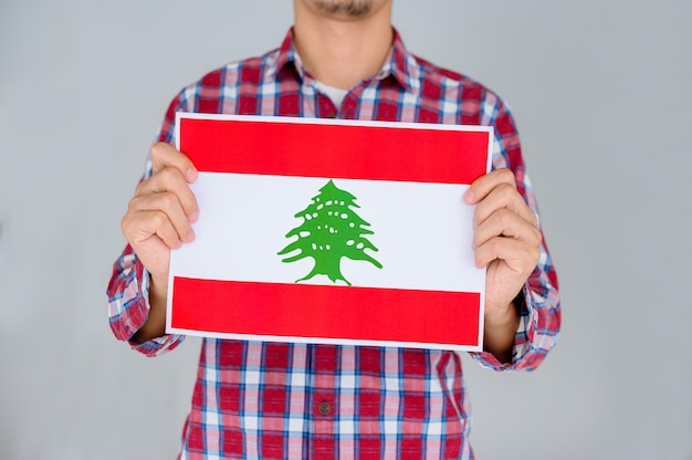 Man in a striped shirt holding the flag of lebanon.
