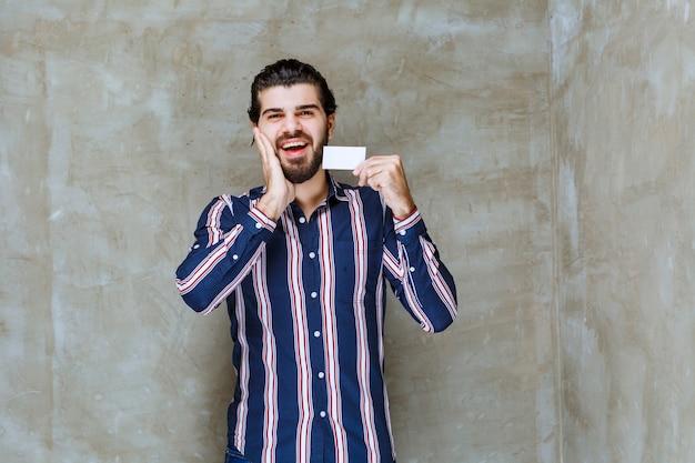 Uomo in camicia a righe che tiene il suo biglietto da visita e si sente sorpreso