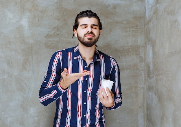 Man in striped shirt holding a white disposable water cup and smelling the flavour