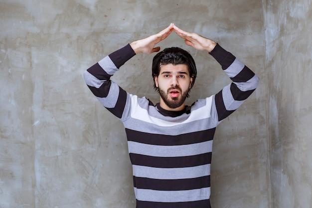 Uomo in camicia a righe che si fa il tetto sopra la testa