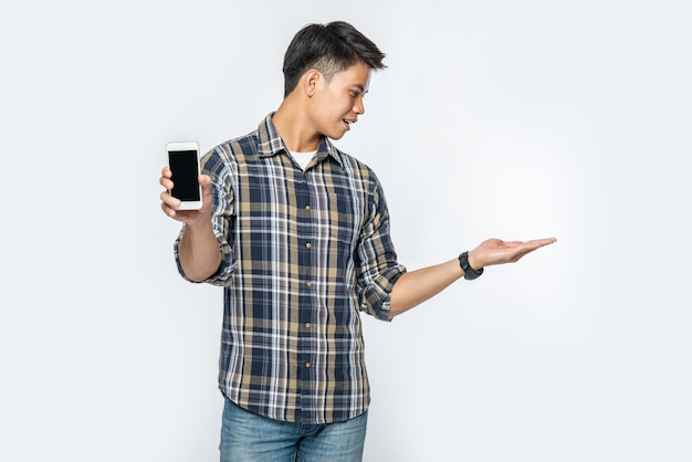 A man in a striped shirt opens his left hand and holds a smartphone