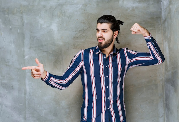 Man in striped shirt showing her fists and feeling strong.