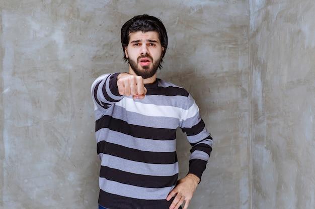 Uomo in camicia a righe che mostra il pugno