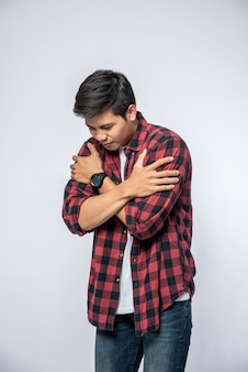 A man in striped shirts stood sick and folded his arms around.