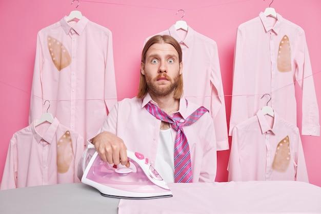 L'uomo accarezza i vestiti usa il flusso elettrico il ferro indossa la camicia e la cravatta intorno al collo ha molto lavoro da fare in pose sul rosa