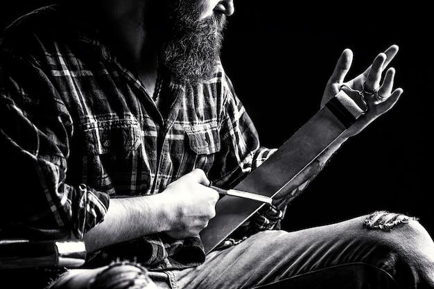革の道具でストレートかみそりをなでる男。西洋かみそり。床屋、かみそり、革のブラシ、かみそりの刃で刃を研ぐためのヴィンテージツール。黒と白。