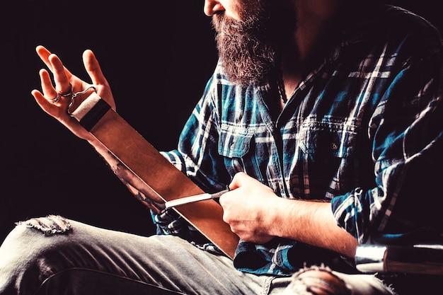 革の道具でストレートかみそりをなでる男。ストレートかみそり、理髪店、あごひげ、刃。西洋かみそり。床屋、かみそり、革のブラシ、かみそりの刃で刃を研ぐためのヴィンテージツール。