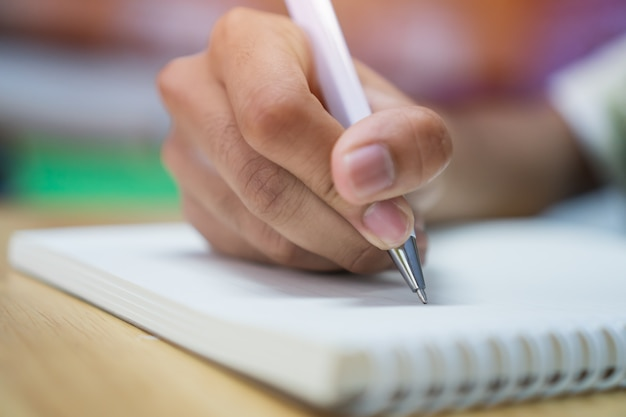 Man student taking writing notes on notebook with pen in library at college university