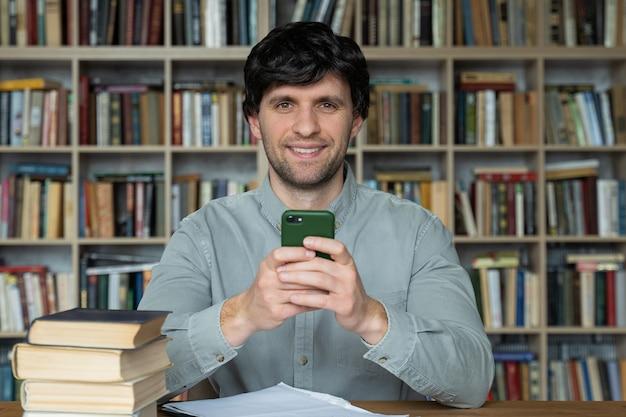 Студент человек с помощью смартфона обучения, сидя за книгами в библиотеке университета