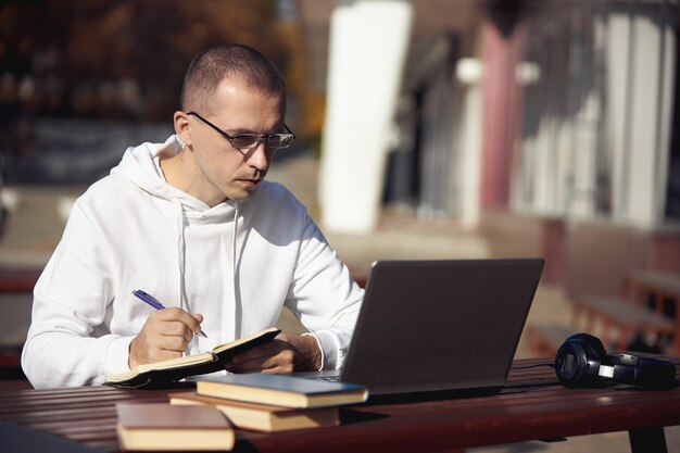 Человек учится на ноутбуке и пишет в блокноте, сидя на улице за столом. социальное дистанцирование во время коронавируса