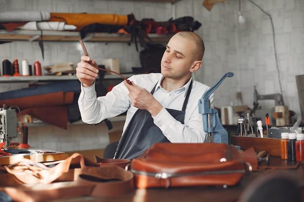 Man in a studio creates leather ware