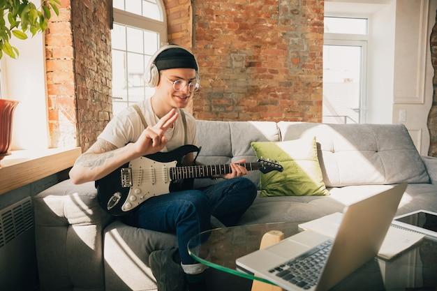 Человек учится дома во время музыкальных онлайн-курсов.