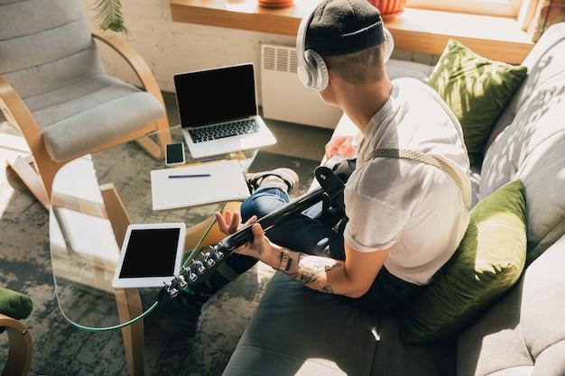 オンラインコースや無料の情報を自分で自宅で勉強している男性。孤立している間はミュージシャン、ギタリストになり、コロナウイルスの拡散を隔離します。ノートパソコン、スマートフォン、ヘッドホンを使用。