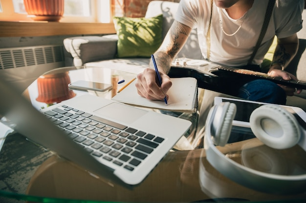 Man studying at home during online courses or free information by hisself. becomes musician, guitarist while isolated, quarantine against coronavirus spreading. using laptop, smartphone, headphones.