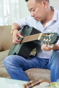 Man studying to play guitar