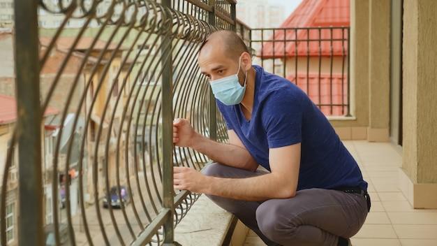 世界的大流行の最中に不安に苦しんでいる男は、アパートのバルコニーに座って通りを見ています