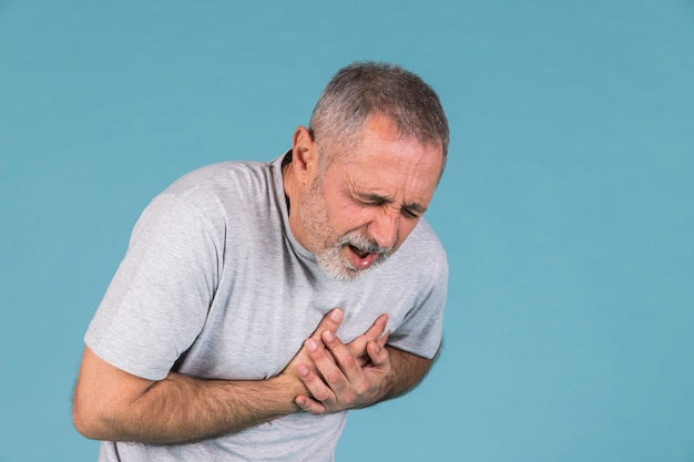 Man suffering from chest pain on blue backdrop
