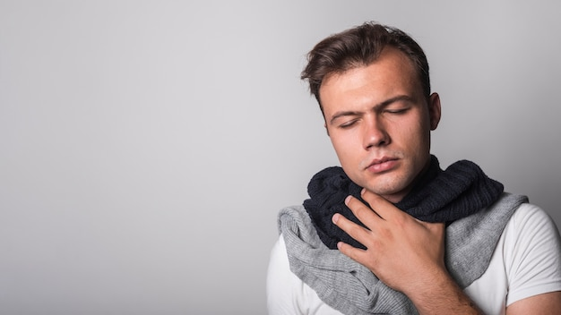 Man suffering from cold against gray background