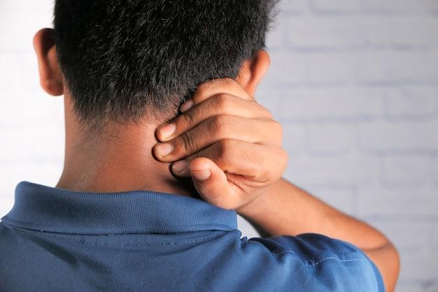 自宅で首や肩の痛みに苦しんでいる男性。
