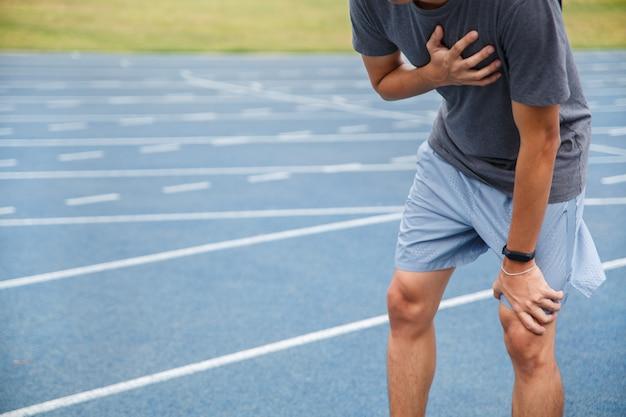 Человек страдает от болезненной груди или симптомов сердечных заболеваний во время бега по синей прорезиненной беговой дорожке.