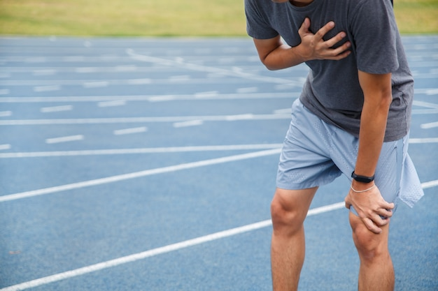 Man suffering from painful chest or symptoms of heart disease while running on the blue rubberized running track.